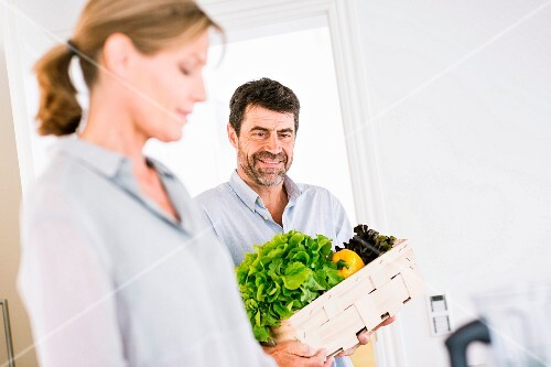A middle-aged couple with a crate of vegetables in a kitchen
