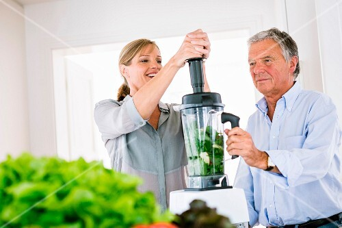 A man and a woman making a vegetable smoothie in a kitchen
