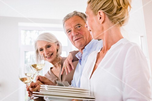 Three older people in a kitchen toasting with wine
