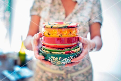 A woman holding a stack of colourful ceramic bowls