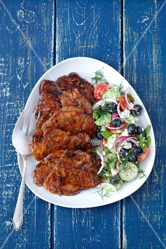 Grilled pork collar served with salad with black olives, tomatoes and feta cheese