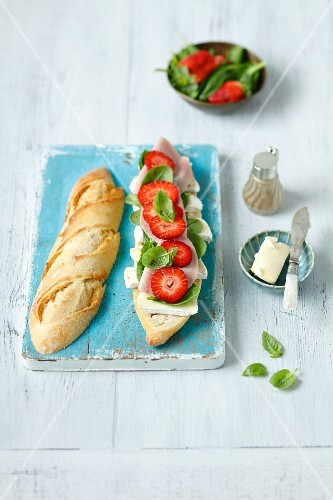 A baguette sandwich with spinach, basil, ham, Camembert and strawberries