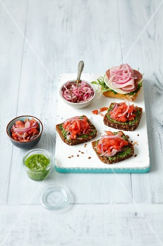 Wholemeal bread topped with basil pesto and tomato salad, and ciabatta topped with Provolone, salami, ham and pickled onions