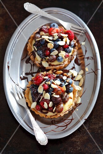 Shortcrust tartlets with vanilla cream, summer berries, flaked almonds and chocolate glaze