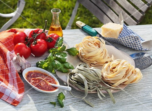 Tagliatelle, tomato sauce and ingredients on a garden table