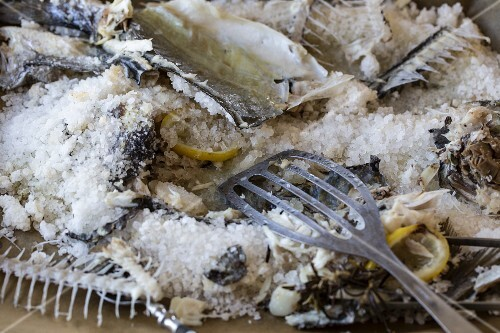 The remains of sea bream in a salt coating on a baking tray