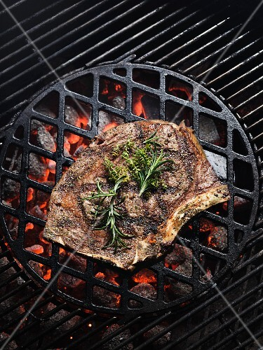 A rib-eye steak with herbs on a barbecue