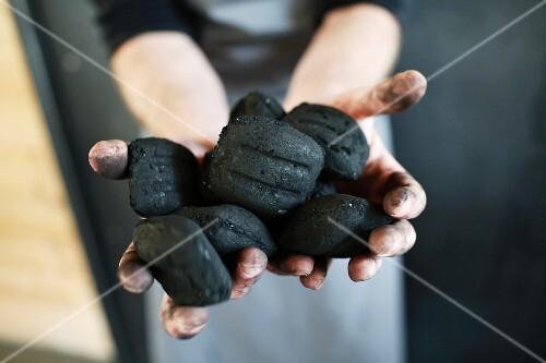 A woman holding charcoal briquettes