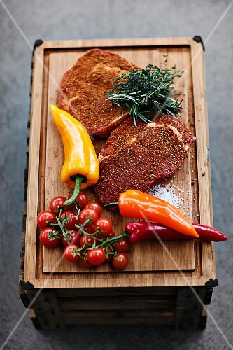 Spiced beefsteak for grilling with vegetables and herbs on a chopping board