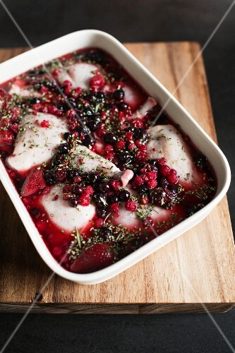 Raw chicken legs in a wild berry marinade