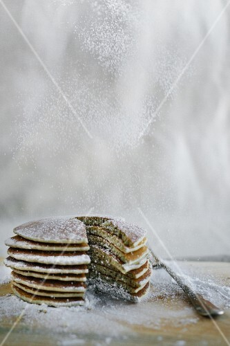 A stack of pancakes being dusted with dancing sugar