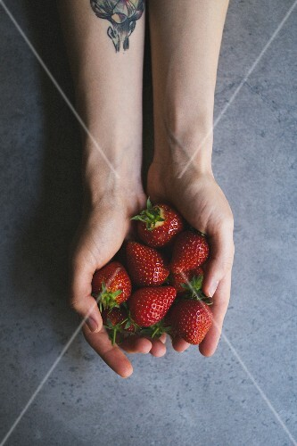 A woman holding strawberries
