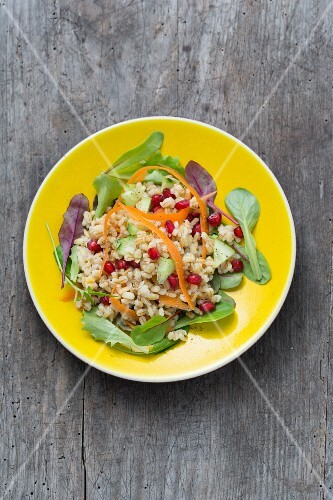 Pearl barley salad with pomegranate seeds and vegetables on a bed of lettuce
