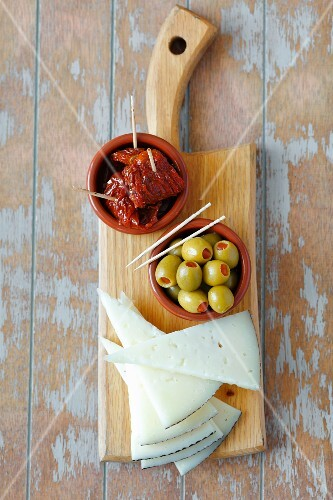 Triangles of Spanish cheese, stuffed olives and dried tomatoes (Spain)