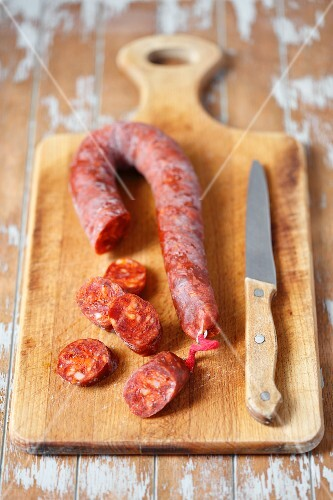 Chorizo on wooden board with a knife