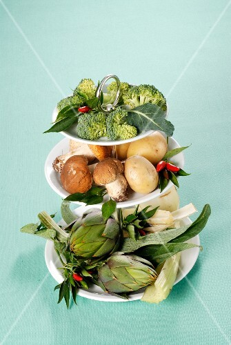 An arrangement of vegetables and mushrooms on a cake stand