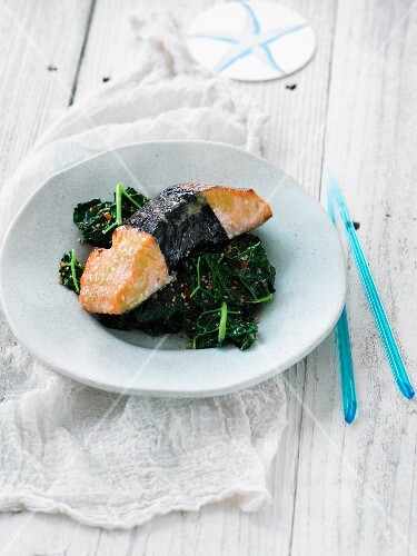 Salmon wrapped in nori on a bed of kale