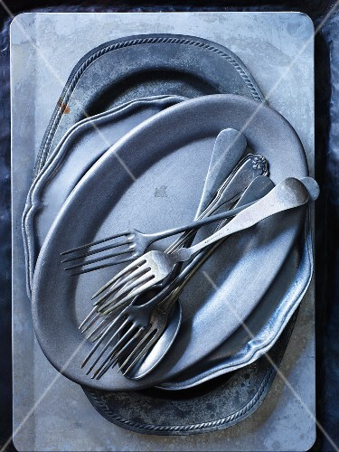 A stack of silver plates and cutlery