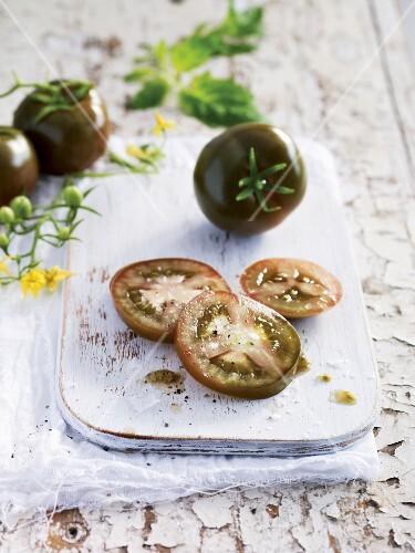Dark kumato tomatoes, whole and sliced
