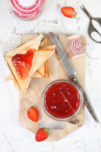 Selbstgemachte Erdbeermarmelade in Einmachglas und auf Toastbrotecken