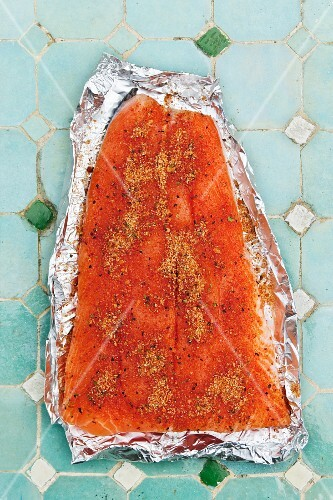 Salmon sprinkled with grilling spices on a piece of aluminium foil