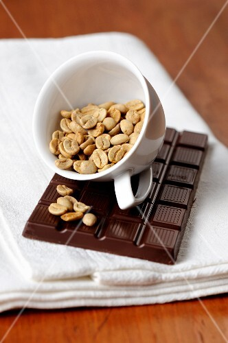 A bar of chocolate and a cup of coffee beans
