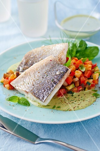 Branzini on colourful diced vegetables with a herb sauce