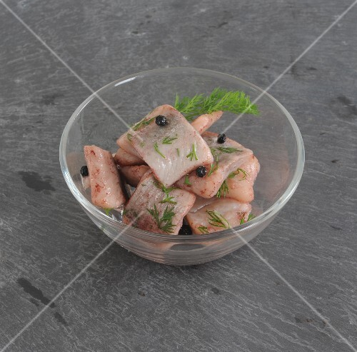 Herring fillet with dill in a glass bowl