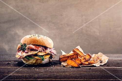 A sesame seed roll with flank steak, red onions and spinach served with sweet potato chips