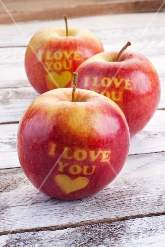 Three red apples carved with hearts and the words 'I love you'