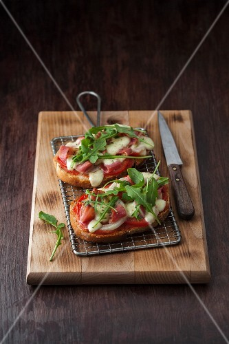 Bruschetta topped with Parma ham, mozzarella, tomatoes, olives and rocket