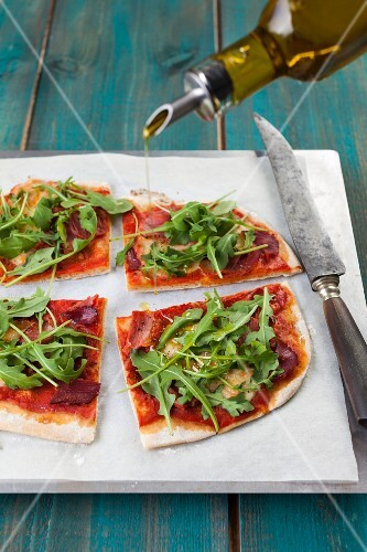 Pizza with rockets, ham, tomatoes and olive oil