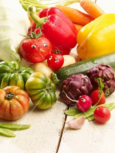 An arrangement of summer vegetables featuring tomatoes with faces