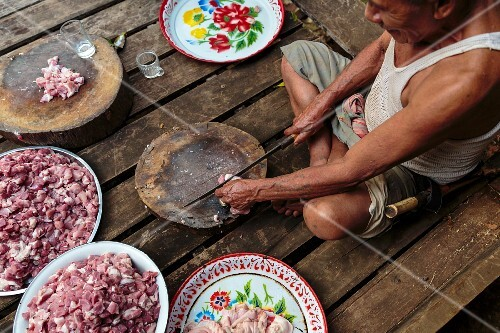 An old man chopping pork on a rustic wooden chopping board, Mae Hong Son, Thailand