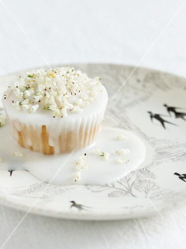 A cupcake with white icing and flowers