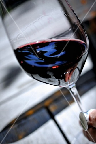 A glass of red wine held at an angle