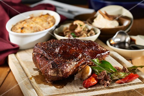 Juicy roasted tri-tip on a chopping board with side dishes