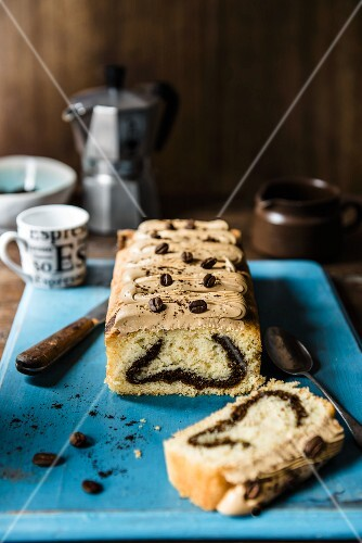 Coffee cake with coffee icing on a blue board, sliced