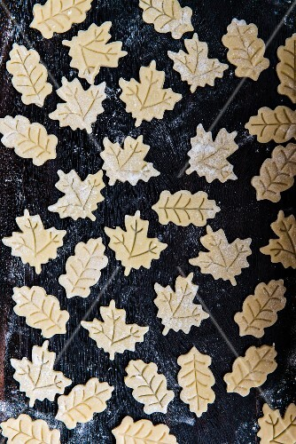 Leaf-shaped biscuits on a baking tray (raw)