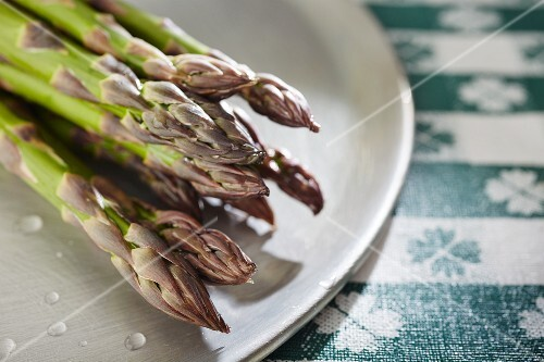Fresh green asparagus on plate (close-up)