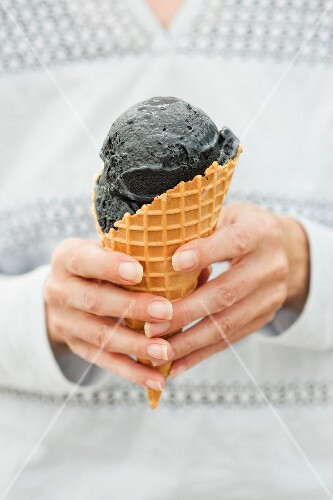 A hand holding black ice cream in a conr