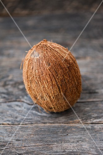 A whole coconut on a wooden surface