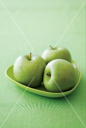 Three Granny Smith apples on a green plate on a green surface