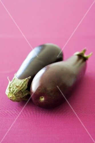 Two aubergines on a pink surface