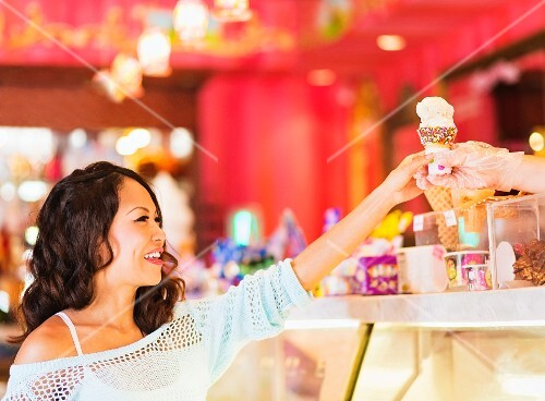 An Oriental woman buying an ice cream at an ice cream stand