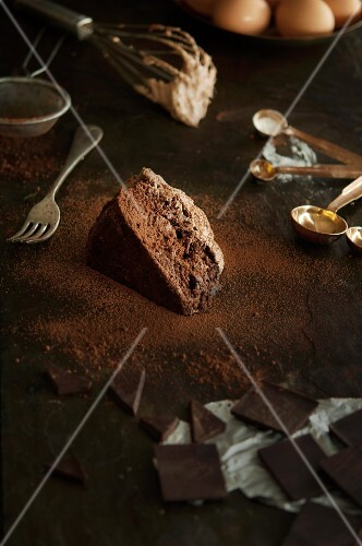 A slice of chocolate cake, baking ingredients and utensils