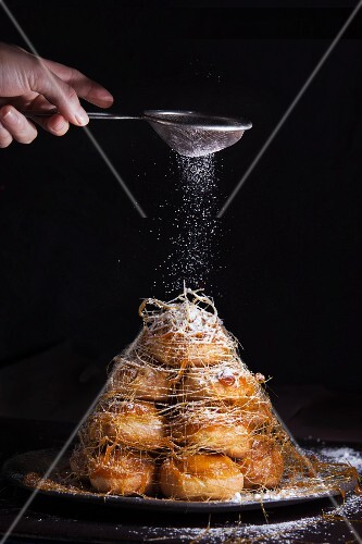 A croquembouche being dusted with icing sugar