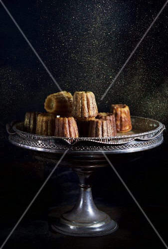 Cannelles being dusted with sugar