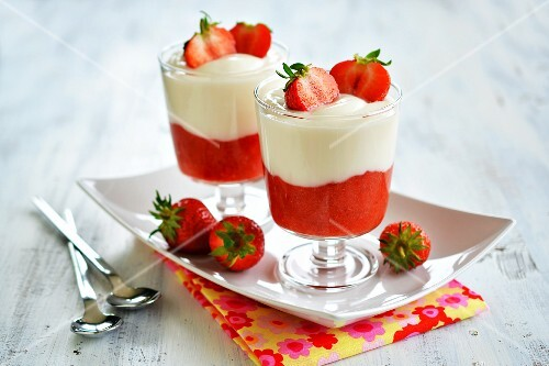 Desserts made with strawberry mousse and yoghurt in glasses on a tray garnished with fresh fruit
