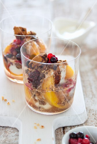 Yoghurt dessert with peaches, berries, biscuits and syrup